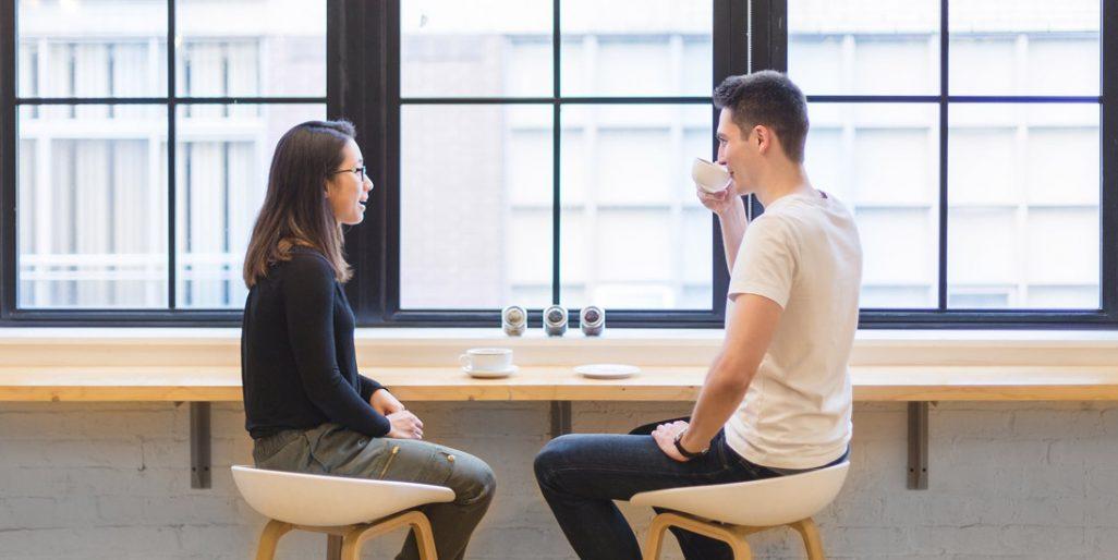 Dva lidé diskutují práci u kávy.